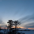 列車と寒い月の見える夕景